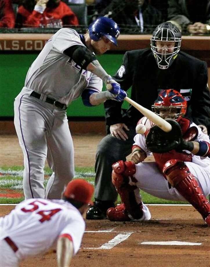 Texas Rangers' Josh Hamilton hits a RBI single off a pitch from St. Louis Cardinals' Jaime Garcia during the first inning of Game 6 of baseball's World Series Thursday, Oct. 27, 2011, in St. Louis. (AP Photo/Jeff Roberson) Photo: Associated Press