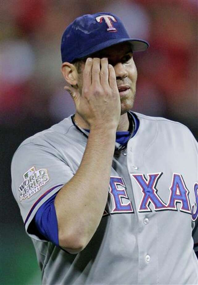 Texas Rangers starting pitcher Colby Lewis reacts after giving up a two-run home run to St. Louis Cardinals' Lance Berkman during the first inning of Game 6 of baseball's World Series Thursday, Oct. 27, 2011, in St. Louis. (AP Photo/Matt Slocum) Photo: Associated Press