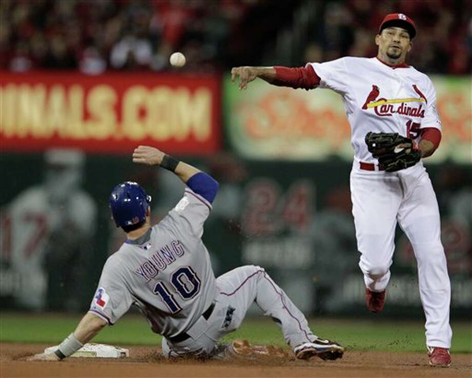 St. Louis Cardinals' Rafael Furcal (15) turns a double play as Texas Rangers' Michael Young (10) slides into second on a ball hit by Adrian Beltre during the third inning of Game 6 of baseball's World Series Thursday, Oct. 27, 2011, in St. Louis. (AP Photo/Charlie Riedel) Photo: Associated Press