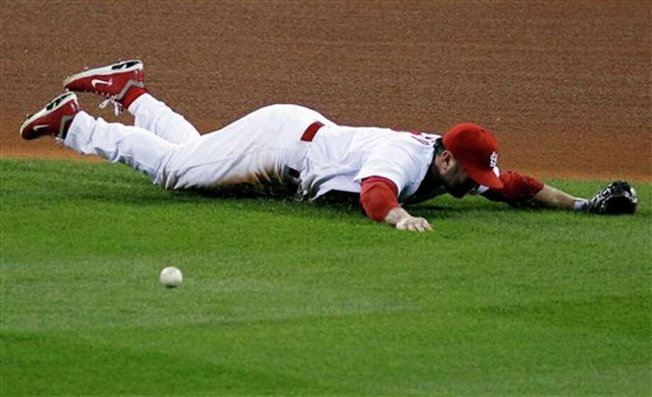 St. Louis Cardinals' Nick Punto misses the ball giving a single to Texas Rangers' Michael Young during the third inning of Game 6 of baseball's World Series Thursday, Oct. 27, 2011, in St. Louis. (AP Photo/Jeff Roberson) Photo: Associated Press
