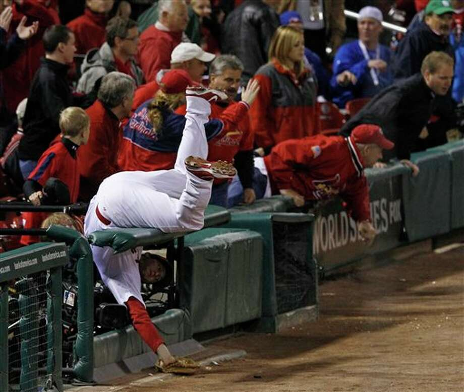 St. Louis Cardinals' David Freese flips over a railing as he goes after a foul ball off the bat of Texas Rangers' Josh Hamilton during the third inning of Game 6 of baseball's World Series Thursday, Oct. 27, 2011, in St. Louis. (AP Photo/Eric Gay) Photo: Associated Press