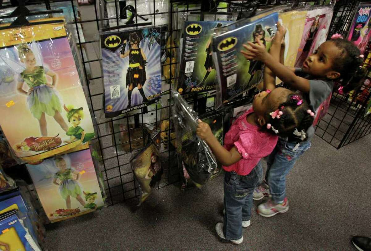 Melissa Phillip Photos : Chronicle FOR THE YOUNG: Jaida Bailey, 2, left, and her sister Journey Bailey, 3, of Rosenberg, look at Batgirl costumes at a Halloween Express store on the Southwest Freeway in Sugar Land. Halloween Express has six pop-up stores in the area.