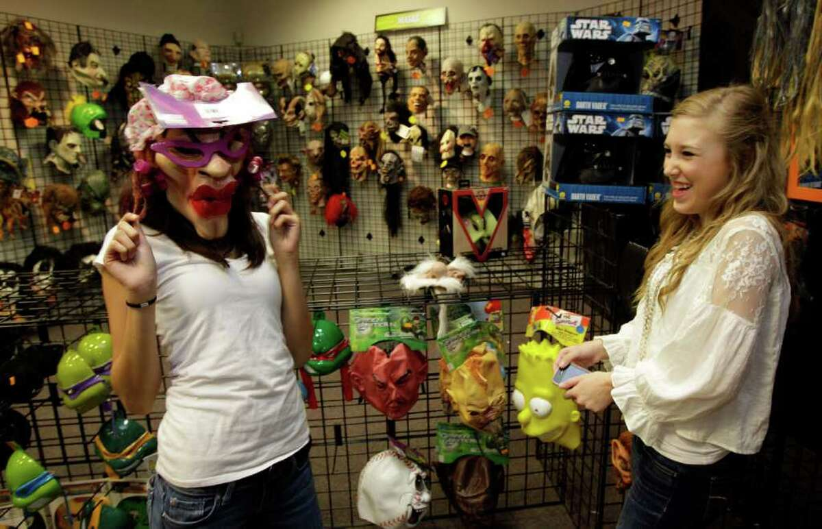 SCARING UP SALES: Nadia Khan, left, and Maddie Marlow, both 16 and from Sugar Land, have fun trying on masks at Halloween Express.