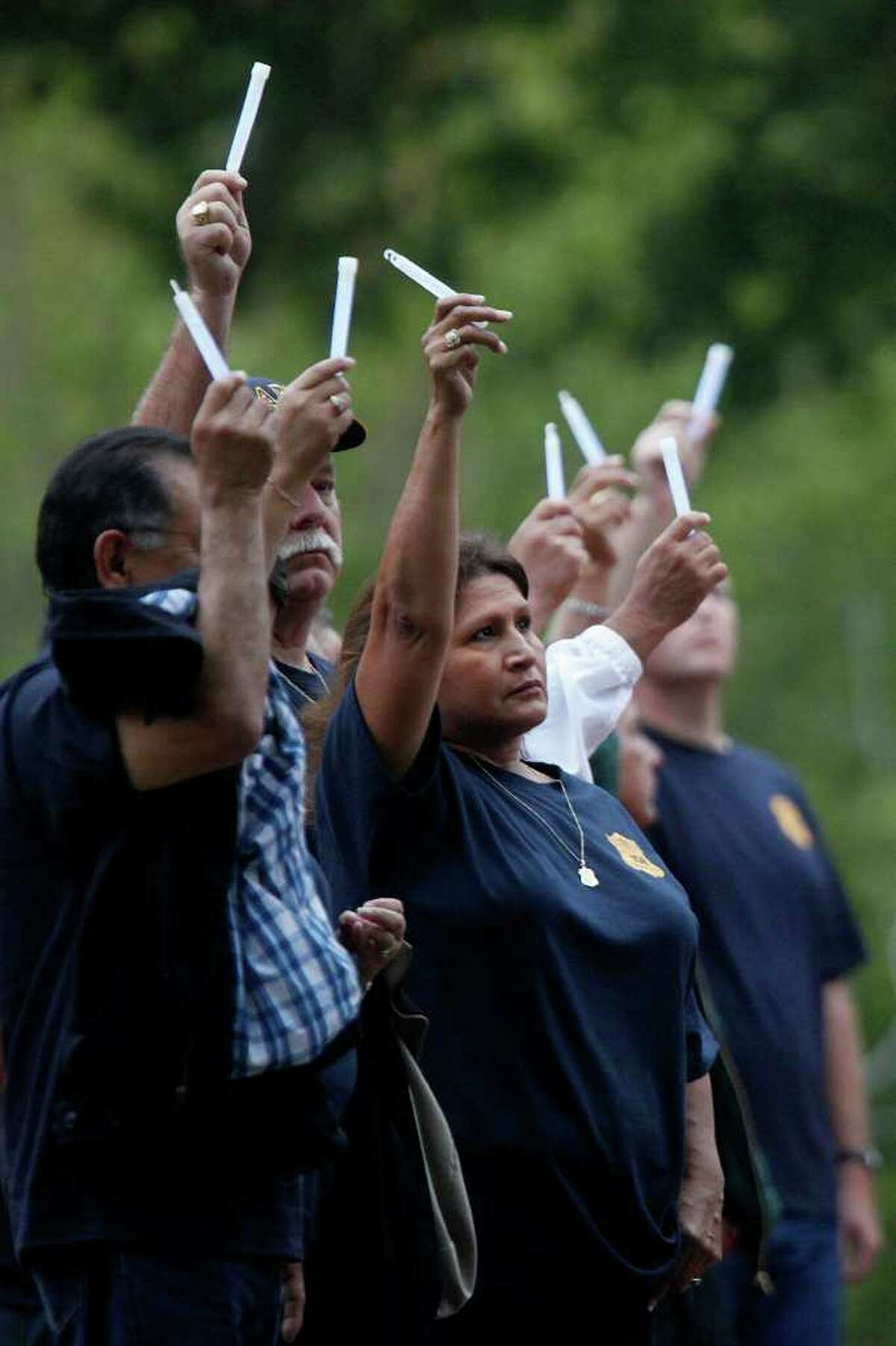 Elo Anders (center), who went to school with San Antonio Police Officer Hector Garza's widow, and others hold up glow sticks on Thursday, Oct. 27, 2011, before the execution of Frank Garcia, who killed Garza in 2001.