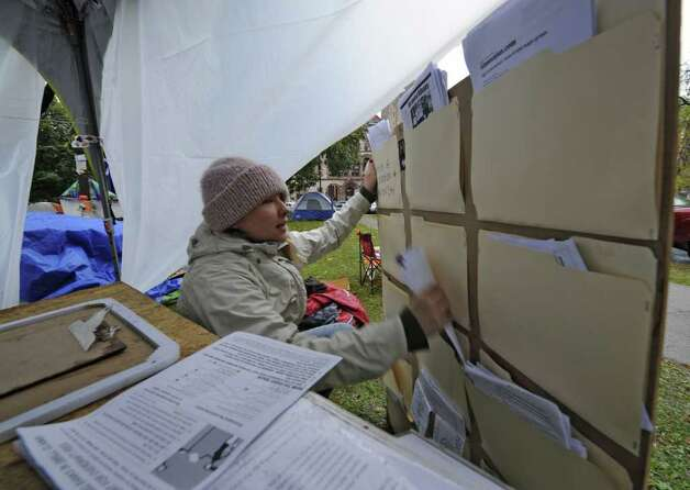 As the rain fell Victoria Ramos set up an information center at the Occupy Albany tent city in Academy Park in Albany, N.Y. October 26, 2011. (Skip Dickstein/Times Union) Photo: Skip Dickstein / 2011