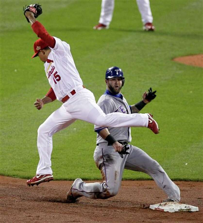 Texas Rangers' Mike Napoli turns his ankle at second as the ball gets past St. Louis Cardinals' Rafael Furcal during the fourth inning of Game 6 of baseball's World Series Thursday, Oct. 27, 2011, in St. Louis. (AP Photo/Jeff Roberson) Photo: Express-News