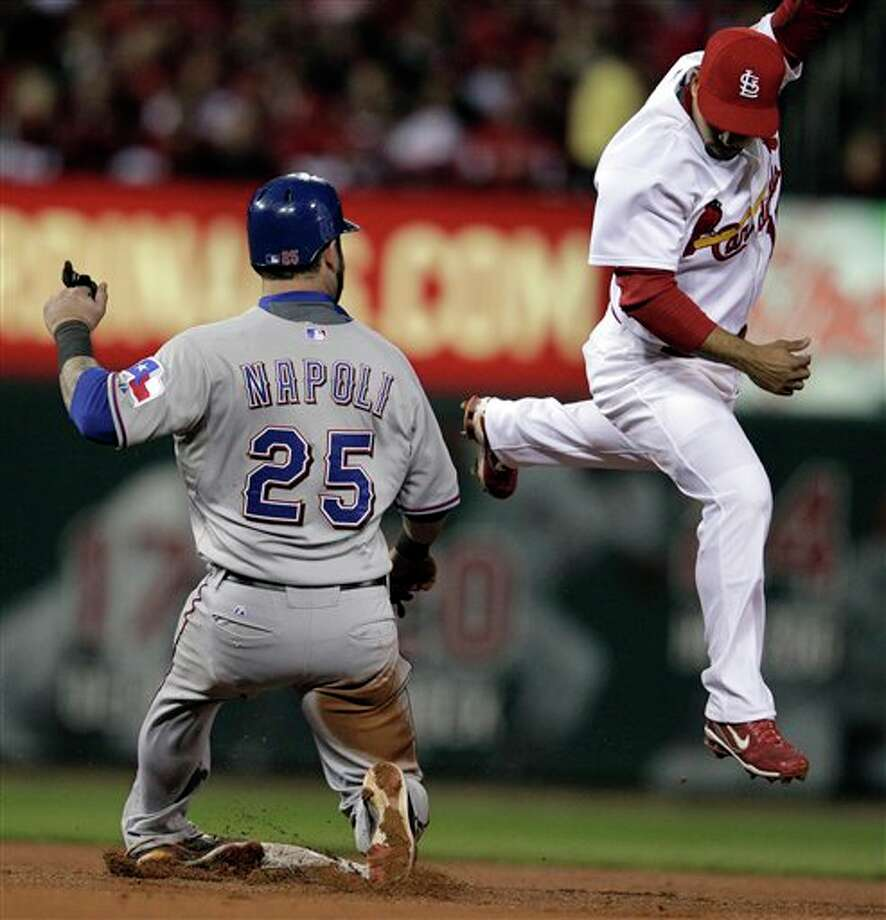 Texas Rangers' Mike Napoli twists his ankle as he slides into second with St. Louis Cardinals' Rafael Furcal covering during the fourth inning of Game 6 of baseball's World Series Thursday, Oct. 27, 2011, in St. Louis. (AP Photo/Charlie Riedel) Photo: Express-News