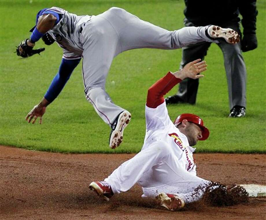 St. Louis Cardinals' Matt Holliday breaks up a double play attempt by Texas Rangers' Elvis Andrus during the fourth inning of Game 6 of baseball's World Series Thursday, Oct. 27, 2011, in St. Louis. (AP Photo/Jeff Roberson) Photo: Express-News