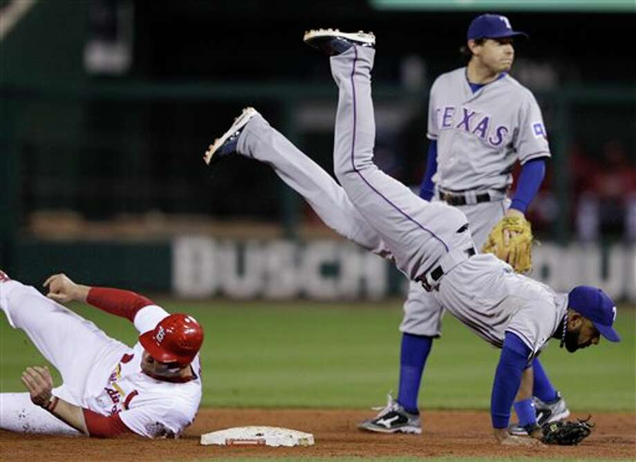 Texas Rangers' Elvis Andrus flips over St. Louis Cardinals' Matt Holliday (7) as he tries to throw out David Freese during the fourth inning of Game 6 of baseball's World Series Thursday, Oct. 27, 2011, in St. Louis. Freese beat the throw. (AP Photo/Matt Slocum) Photo: Express-News
