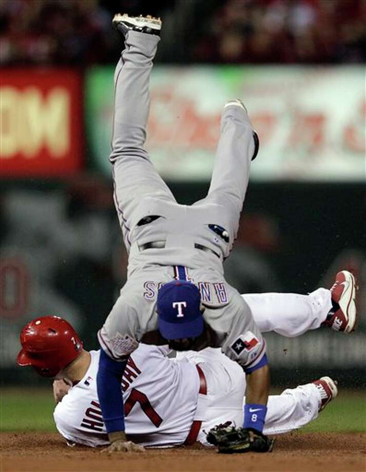 Texas Rangers' Elvis Andrus flips over St. Louis Cardinals' Matt Holliday (7) as he tries to throw out David Freese during the fourth inning of Game 6 of baseball's World Series Thursday, Oct. 27, 2011, in St. Louis. Freese beat the throw. (AP Photo/Charlie Riedel) Photo: Express-News