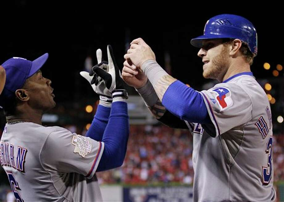 Texas Rangers' Josh Hamilton, right, is congratulated by Esteban German (6) after scoring during the fifth inning of Game 6 of baseball's World Series against the St. Louis Cardinals Thursday, Oct. 27, 2011, in St. Louis. (AP Photo/Matt Slocum) Photo: Express-News