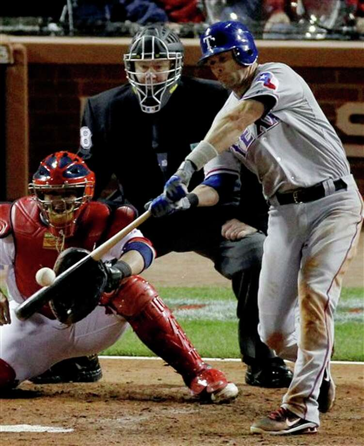 Texas Rangers' Michael Young hits a RBI double during the fifth  inning of Game 6 of baseball's World Series against the St. Louis Cardinals Thursday, Oct. 27, 2011, in St. Louis. (AP Photo/Jeff Roberson) Photo: Express-News