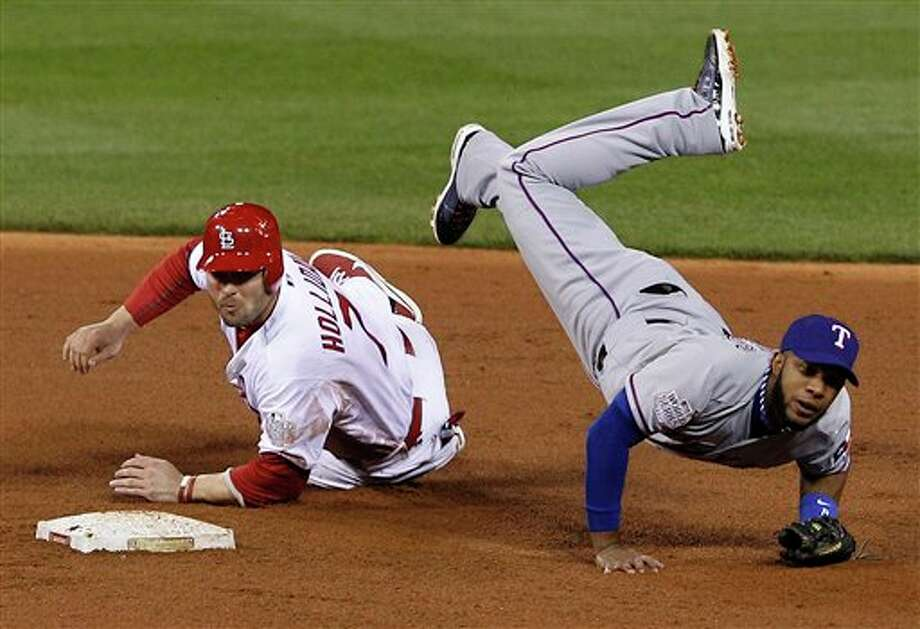 Texas Rangers' Elvis Andrus flips over St. Louis Cardinals' Matt Holliday (7) as he tries to throw out David Freese during the fourth inning of Game 6 of baseball's World Series Thursday, Oct. 27, 2011, in St. Louis. Freese beat the throw. (AP Photo/Eric Gay) Photo: Express-News