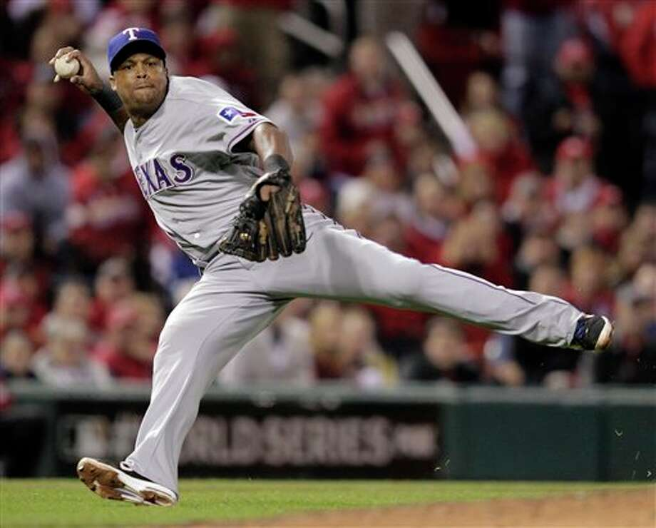 Texas Rangers' Adrian Beltre can't make a play on a ball hit by St. Louis Cardinals' Lance Berkman during the sixth inning of Game 6 of baseball's World Series Thursday, Oct. 27, 2011, in St. Louis. (AP Photo/Charlie Riedel) Photo: Express-News