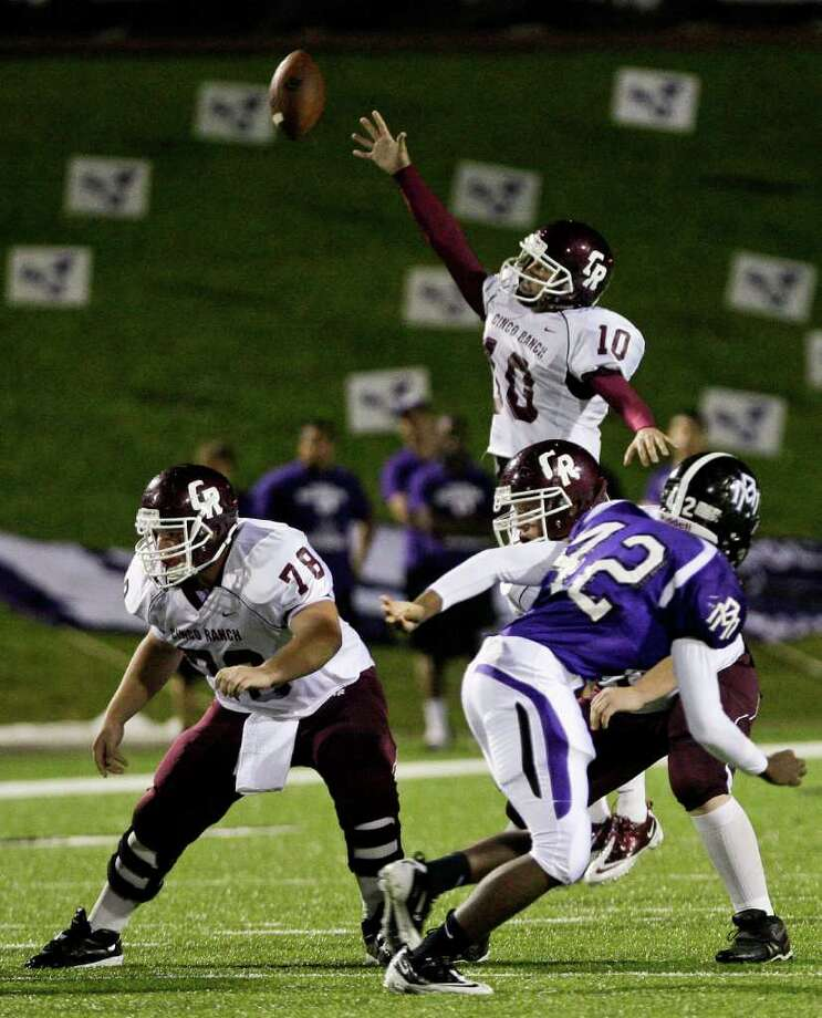 Cinco Ranch quarterback Cole Thomas reaches for the snap as it goes over his head. Photo: For The Chronicle: Thomas B. She