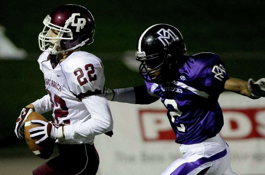 10/27/11: Wid receiver Alex Ludowig #22 of the Cinco Ranch Cougars scores a t29 yard touchdown reception while defensive back Avery Ross #2 of the Mortan Ranch Mavericks gives chase in a district high school football game at Rhodes Stadium in Katy, Texas. Thomas B. Shea Photo: For The Chronicle: Thomas B. She
