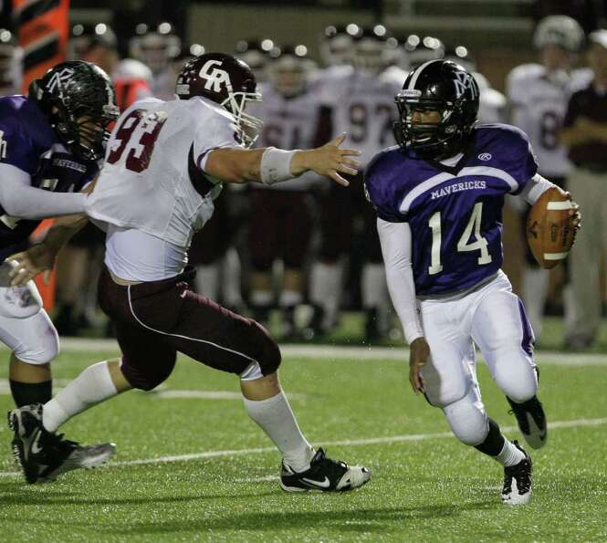 Morton Ranch quarterback Terrion Poittier scrambles out of the reach of Cinco Ranch defensive linema