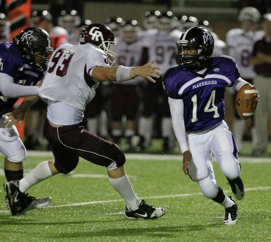 Morton Ranch quarterback Terrion Poittier scrambles out of the reach of Cinco Ranch defensive lineman Cody Newnom. Photo: For The Chronicle: Thomas B. She