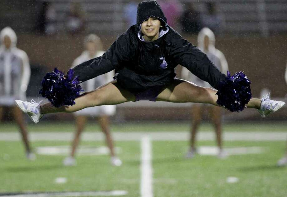 10/27/11: A Cinco Ranch cheerleader is introduced in the rain before the Cinco Ranch Cougars played against  the Mortan Ranch Mavericks in a district high school football game at Rhodes Stadium in Katy, Texas. Thomas B. Shea Photo: For The Chronicle: Thomas B. She