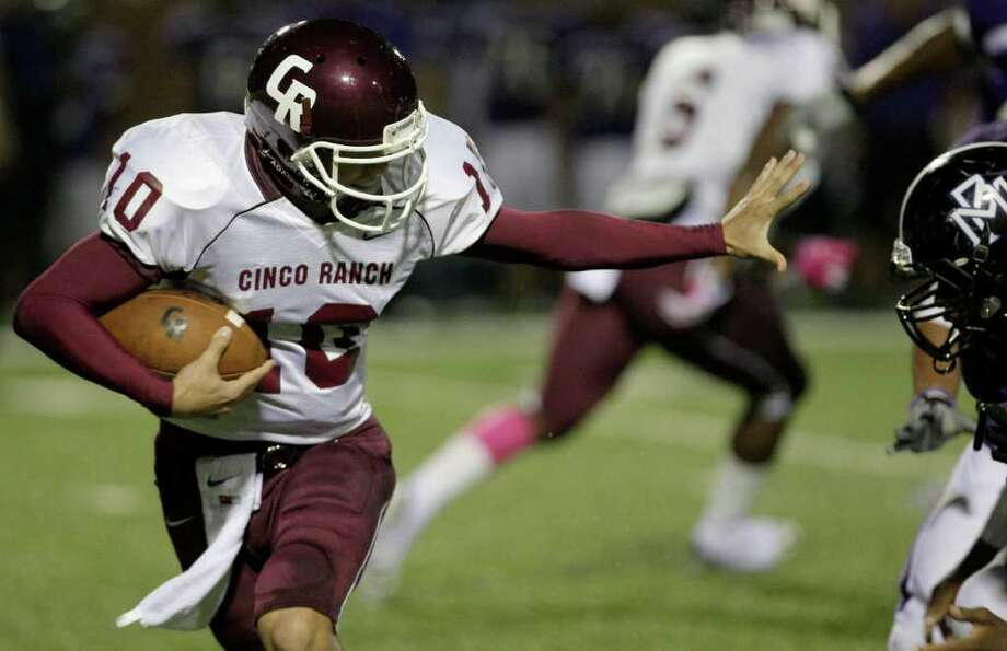 10/27/11: Quarterback Cole Thomas #10 of the Cinco Ranch Cougars stiff arms Mortan Ranch Mavericks defender  in a district high school football game at Rhodes Stadium in Katy, Texas. Thomas B. Shea Photo: For The Chronicle: Thomas B. She
