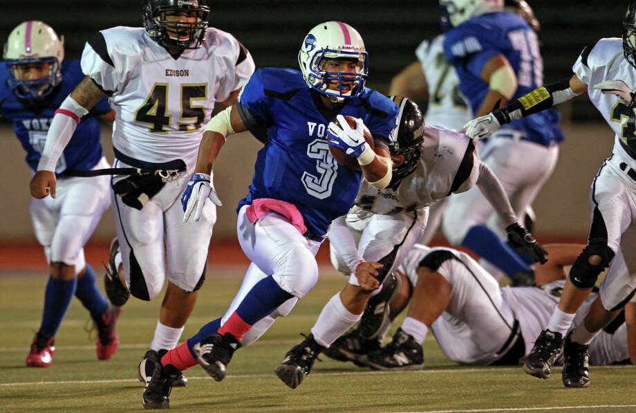Voks running back Isaac Cervantes breaks through a hole in the line for a long touchdown run in the first quarter as Lanier plays Edison at Alamo Stadium on October 27, 2011. Tom Reel/Staff Photo: TOM REEL, SAN ANTONIO EXPRESS-NEWS / © 2011 San Antonio Express-News