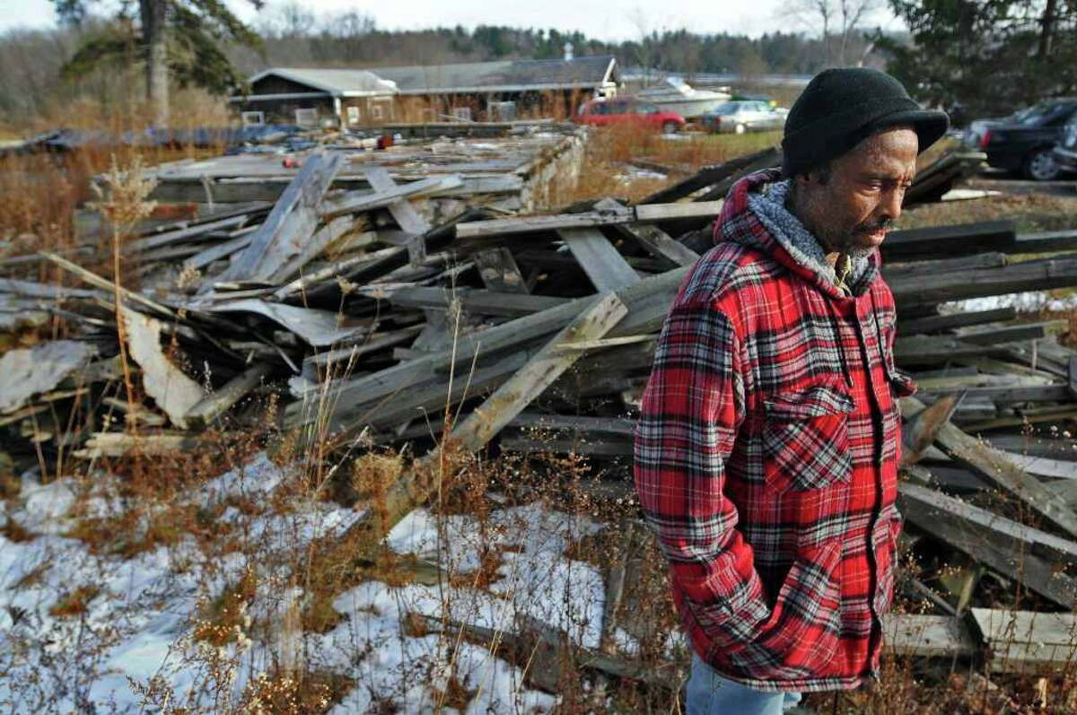Gerard Carter used insurance money from his burned house to invest in a scam that lost Carter thousands of dollars. He stands next to the remains of the house in New Baltimore, NY on Thursday January 6, 2011. He still pays $1800 a month for a mortgage on the destroyed house, despite his losses. The scam is part of a federal prosecution. ( Philip Kamrass / Times Union )