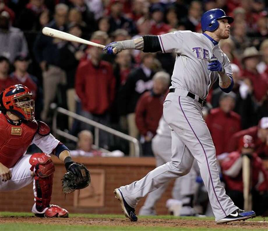 St. Louis Cardinals catcher Yadier Molina watches as Texas Rangers' Josh Hamilton hits a two-run home run during the 10th inning of Game 6 of baseball's World Series Thursday, Oct. 27, 2011, in St. Louis. (AP Photo/Charlie Riedel) Photo: Associated Press