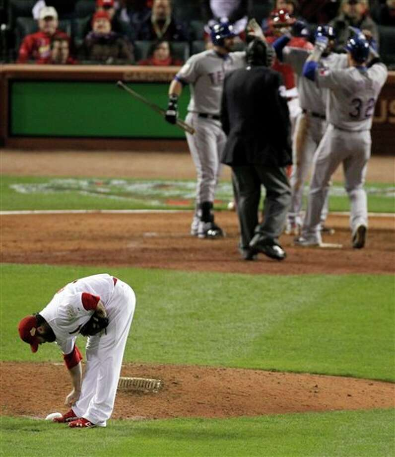 St. Louis Cardinals' Jason Motte makes an adjustment after giving up a two-run home run to Texas Rangers' Josh Hamilton during the tenth inning of Game 6 of baseball's World Series Thursday, Oct. 27, 2011, in St. Louis. (AP Photo/Jeff Roberson) Photo: Associated Press