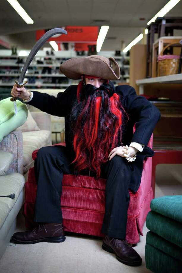 """Orion Mcafee models a """"Pirate"""" costume -sword: new item $7.99 -pirate hat: new item $7.99 -waist sash: used item $2.99 -long black coat: used item $9.99 -red/black wig converted into a beard: new item $6.99 -black pants: models own -black shirt: models own  about $36  Photographed at the Crown Hill Value Village on Thursday, October 27, 2011. Photo: JOSHUA TRUJILLO / SEATTLEPI.COM"""