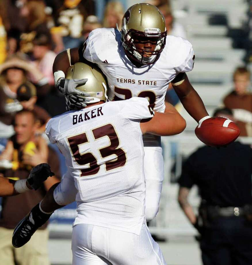 Texas State running back Terrence Franks is lifted up by teammate Devin Baker while celebrating his touchdown run against Wyoming  during an NCAA football game Saturday, Sept. 10, 2011, at War Memorial Stadium in Laramie, Wyo. (AP Photo/Laramie Boomerang, Andy Carpenean) Photo: Associated Press