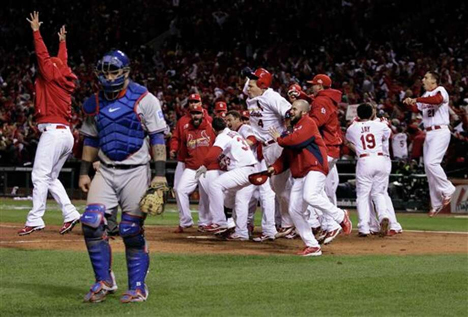 Texas Rangers catcher Mike Napoli walks away as the St. Louis Cardinals celebrate after David Freese hit a walk-off home run during the 11th inning of Game 6 of baseball's World Series Thursday, Oct. 27, 2011, in St. Louis. (AP Photo/Matt Slocum) Photo: Associated Press