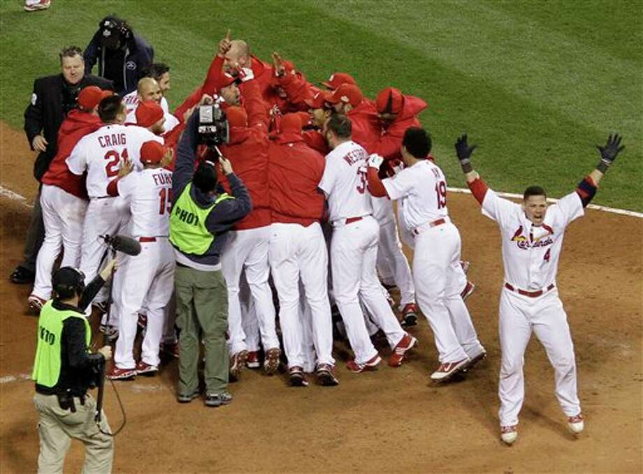 Teammates swarm St. Louis Cardinals' David Freese at home after he hit a walk-off home run during the 11th inning of Game 6 of baseball's World Series against the Texas Rangers Thursday, Oct. 27, 2011, in St. Louis. The Cardinals won the game 10-9 to tie the series 3-3. (AP Photo/Matt Slocum) Photo: Associated Press