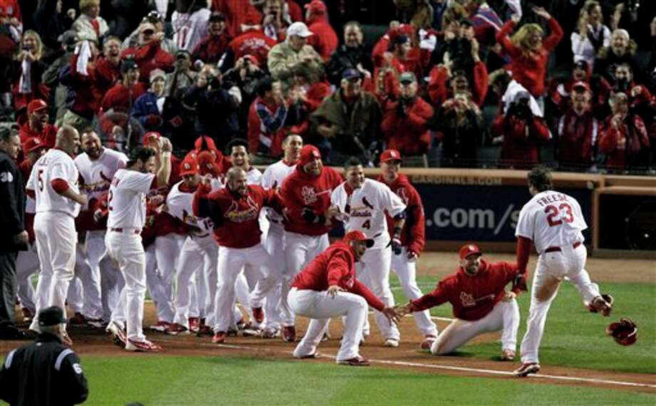 St. Louis Cardinals greet David Freese, right, at home after Freese hit a solo home run off a pitch by Texas Rangers' Mark Lowe in the 11th inning to win Game 6 of baseball's World Series 10-9, Thursday, Oct. 27, 2011, in St. Louis. The series is tied 3-3. (AP Photo/Jeff Roberson) Photo: Associated Press