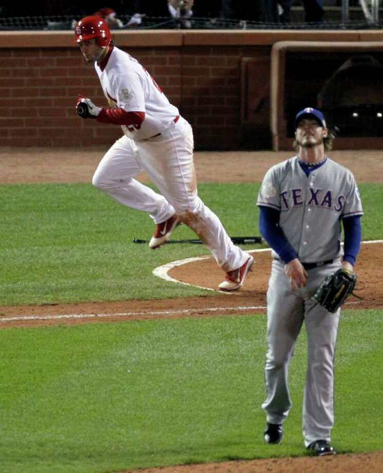 St. Louis' David Freese begins his game-winning home-run trot as Texas' Mark Lowe watches the ball leave the park in the 10th inning Thursday night. Photo: Jeff Roberson / AP