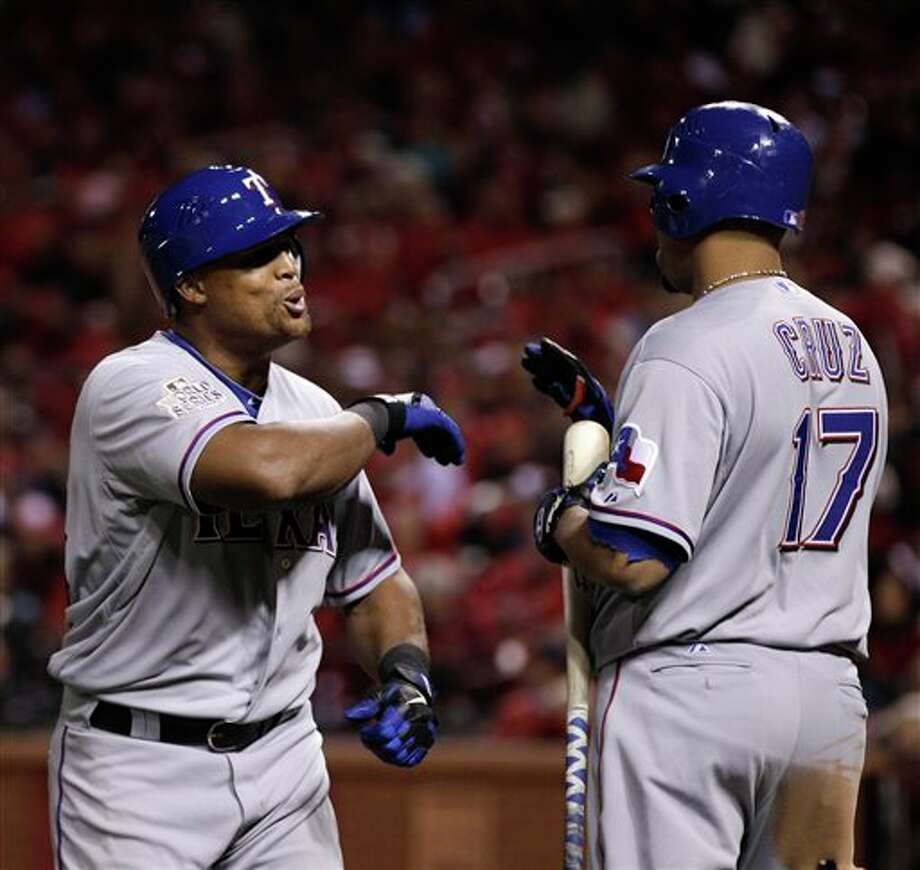Texas Rangers' Adrian Beltre celebrates with Nelson Cruz (17) after Beltre hit a home run during the seventh inning of Game 6 of baseball's World Series against the St. Louis Cardinals Thursday, Oct. 27, 2011, in St. Louis. (AP Photo/Matt Slocum) Photo: Associated Press