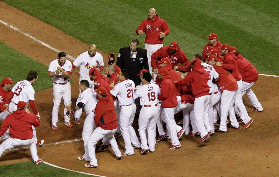 Teammates swarm St. Louis Cardinals' David Freese at home after he hit a walk-off home run during the 11th inning of Game 6 of baseball's World Series against the Texas Rangers Thursday, Oct. 27, 2011, in St. Louis. The Cardinals won the game 10-9 to tie the series 3-3. (AP Photo/Matt Slocum) Photo: Matt Slocum, Associated Press / AP
