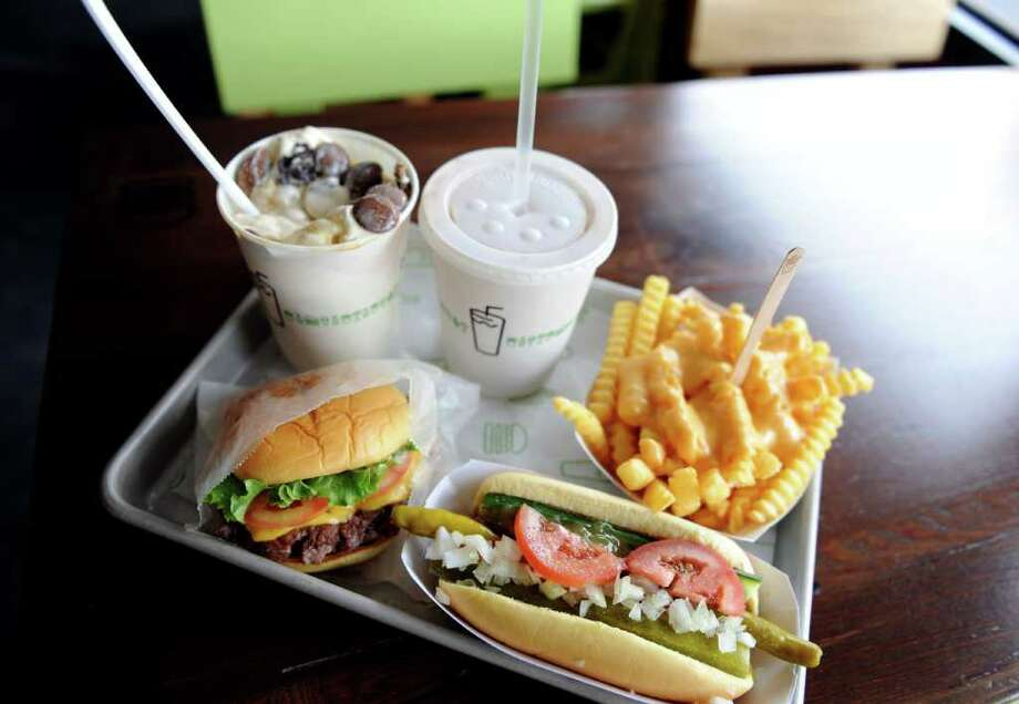 Some of offerings from Shake Shack's menu at the newest location in Westport, Conn.  Clockwise, a Hopscotch Concrete (frozen custard blended with toppings and mix-ins), a black and white shake, cheese fries, a Shack-cago Dog and a ShackBurger. Photo: Autumn Driscoll / Connecticut Post