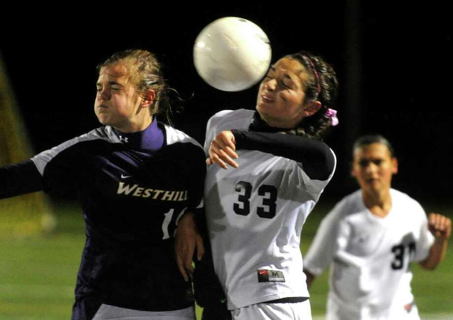 Westhill's #19 Jess Lazlo, left, and Trumbull's #33 Riana Odin head the ball, during girls soccer action Trumbull, Conn. on Thursday October 27, 2011. Photo: Christian Abraham / Connecticut Post