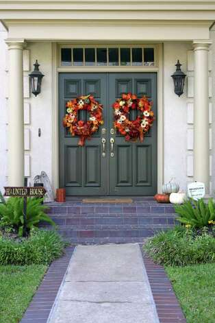 It's easy to transition your door from Halloween to Thanksgiving with bare bones planning and a few simple tweaks. Incorporate pumpkins, wreaths and colors of the harvest with the witches and ghosts. Photo: Melanie Warner Spencer, Halloween Doors / SA
