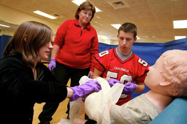 Greenwich High School senior Julia Jandrisits, left, instructor Lil Perone, and J.P. Doyle run through a simulated emergency scenario during the school's new Basic Life Support Emergency Provider Program Friday morning, Oct. 28, 2011. The elective class is run in conjunction with Greenwich Emergency Medical Service and the Greenwich High School Physical Education/Wellness Department. Photo: David Ames / Greenwich Time