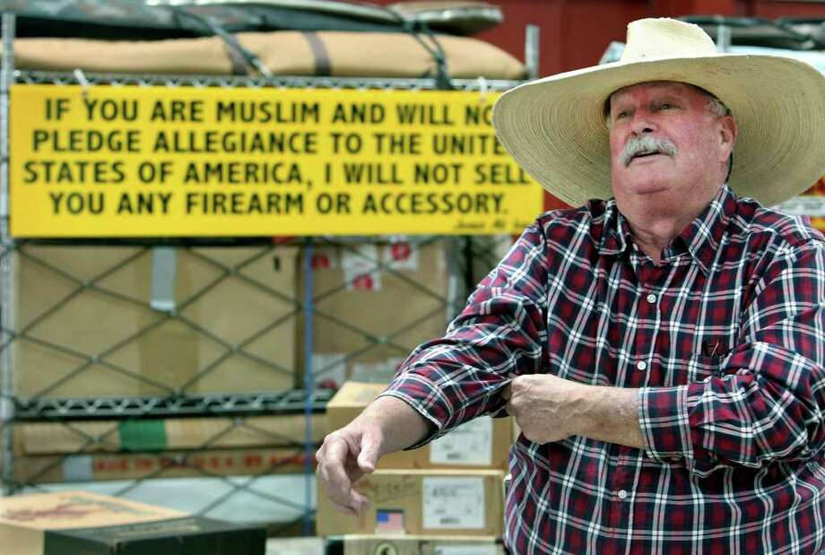 Crockett Keller with the sign that will hang today at his display at the Texas Gun and Knife Show at the Gillespie County Fairgrounds. A radio commercial he made has gone viral on the Internet. Photo: TOM REEL, SAN ANTONIO EXPRESS-NEWS / © 2011 San Antonio Express-News
