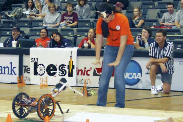 "FORREST M. MIMS III COMPETING: A spotter helps a robot driver drop a ""bug"" into a containment area under the watchful eyes of judges and a referee at the 2011 San Antonio BEST Robotics Competition. Photo: FORREST M MIMS 111"