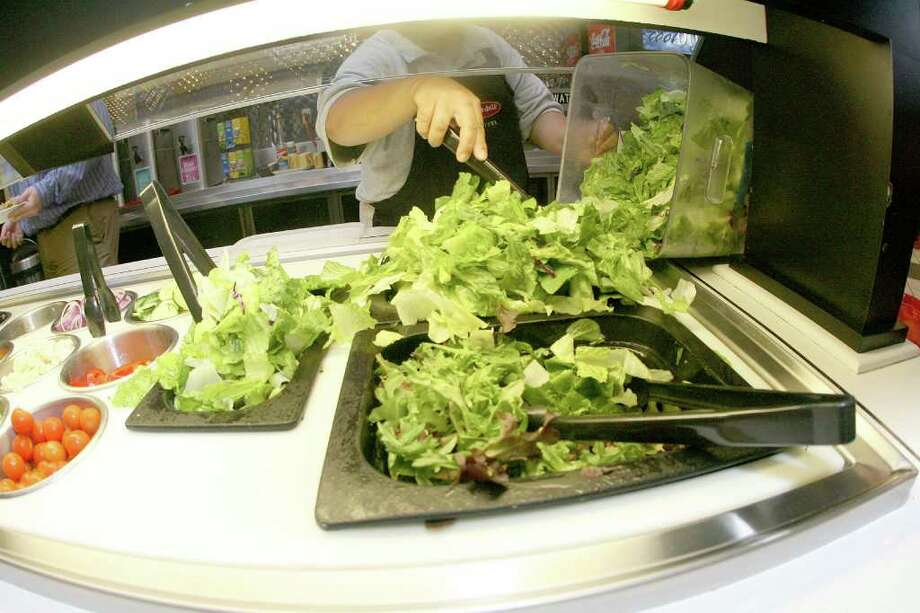 Bill Olive-for the Chronicle. 10/09/06. Maria Luz refreshes the salad bar at the Jason's Deli at 901 McKinney.  Despite the new lettuce scare on the West Coast, salad is still a popular menu choice. Photo: Bill Olive, Freelance / Freelance