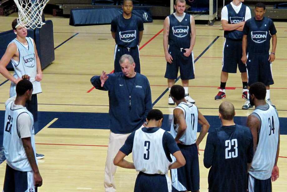 Connecticut head coach Jim Calhoun, center, runs his team through an NCAA college basketball practice at Gampel Pavilion in Storrs, Conn., on Friday, Oct. 28, 1011. Changes in NCAA rules adopted Thursday would keep defending national champion Connecticut from participating in the 2013 NCAA men's basketball tournament, as the school's academic performance of student athletes would fall below the Academic Progress Rate requirement. (AP Photo/Pat Eaton-Robb) Photo: Pat Eaton-Robb, AP / AP
