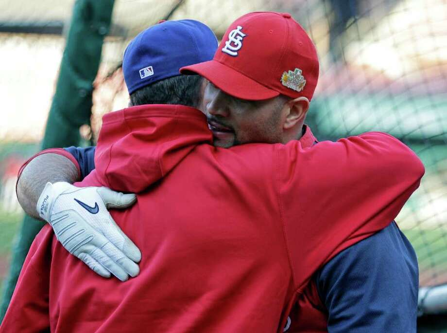 St. Louis Cardinals' Albert Pujols, right, hugs Texas Rangers' Michael Young before Game 7 of baseball's World Series Friday, Oct. 28, 2011, in St. Louis. (AP Photo/Paul Sancya) Photo: Paul Sancya, Associated Press / AP