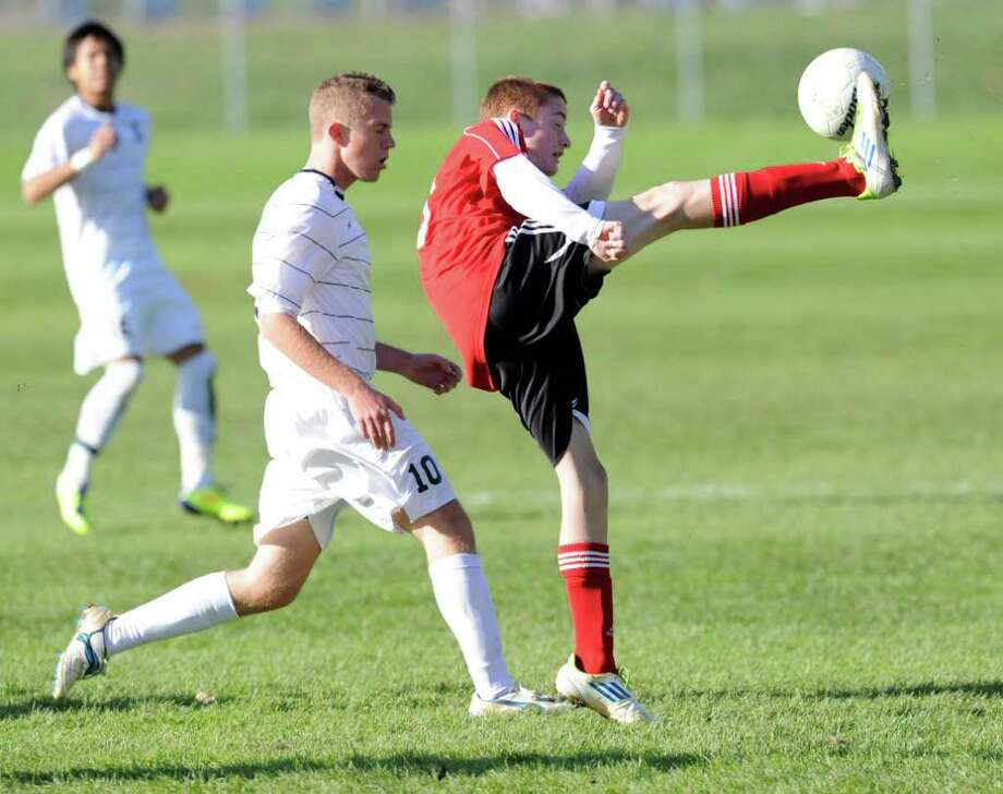 Patrick Santini, right, # 30 of Grenwich High School, kicks the ball downfield as Dylan Evans of Staples High School closes in, during boys high school soccer playoff between Staples High School and Greenwich High School at Staples, Friday afternoon Oct. 28, 2011. Photo: Bob Luckey / Greenwich Time