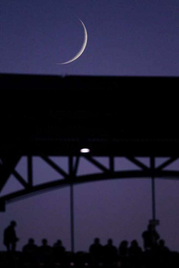 The moon is seen from Busch Stadium before Game 7 of baseball's World Series between the St. Louis Cardinals and the Texas Rangers Friday, Oct. 28, 2011, in St. Louis. (AP Photo/Jeff Roberson) Photo: Jeff Roberson, Associated Press / AP