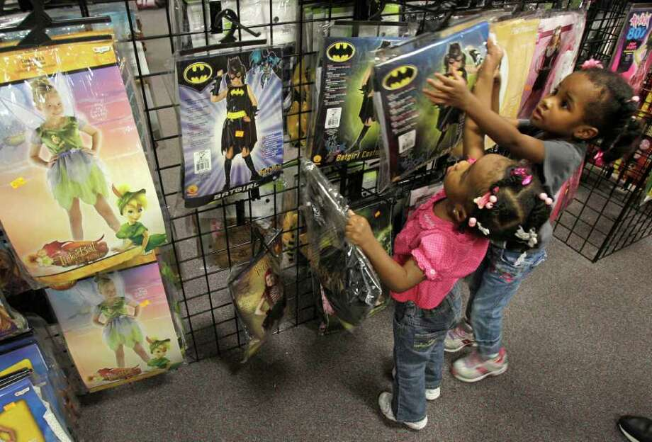Jaida Bailey, 2, left, and her sister, Journey Bailey, 3, of Rosenberg look at  Batgirl costumes at Halloween Express in Sugar Land. Photo: Melissa Phillip, Houston Chronicle / © 2011 Houston Chronicle