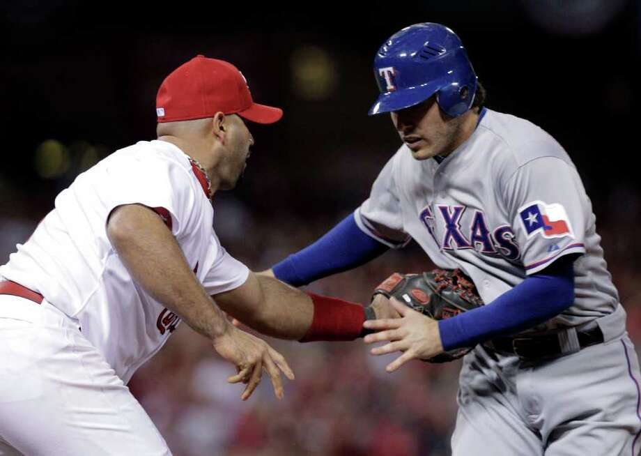 St. Louis Cardinals first baseman Albert Pujols tags out Texas Rangers' Ian Kinsler as he is caught stealing during the first inning of Game 7 of baseball's World Series Friday, Oct. 28, 2011, in St. Louis. (AP Photo/Charlie Riedel) Photo: Charlie Riedel, Associated Press / AP