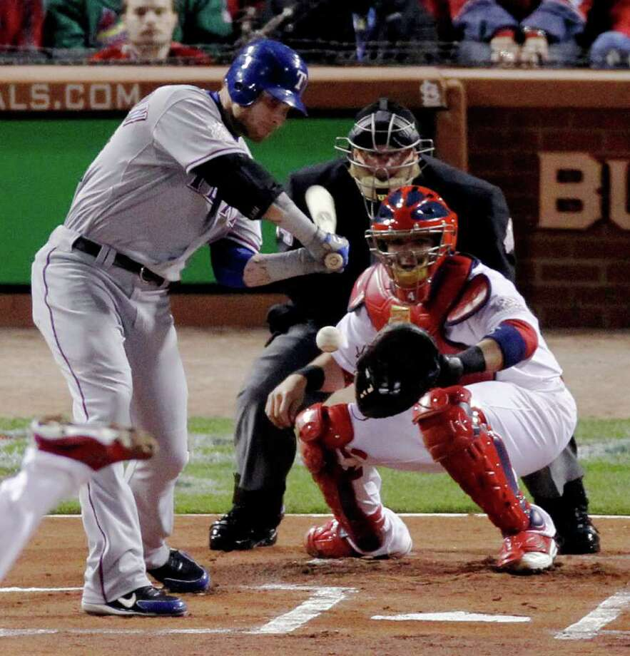 Texas Rangers' Josh Hamilton hits a RBI double off a pitch from St. Louis Cardinals' Chris Carpenter during the first inning of Game 7 of baseball's World Series Friday, Oct. 28, 2011, in St. Louis. (AP Photo/Jeff Roberson) Photo: Jeff Roberson, Associated Press / AP